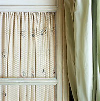 In a London bedroom the floral motif of pleated fabric lining an antique armoire picks out the colour of an adjacent eau-de-nil curtain