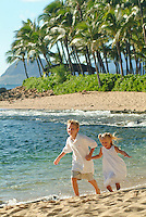 Brother and sister running down the beach holding hands on the west side of Oahu