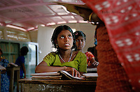Ratna Khatun listens to the teacher during a lesson on a boat school. She lives in the village of Kalinagar by the Atrai river and attends fourth grade. She wants to become a doctor and return to the area to work on the healthcare boat. (Photo by Tadej Znidarcic)