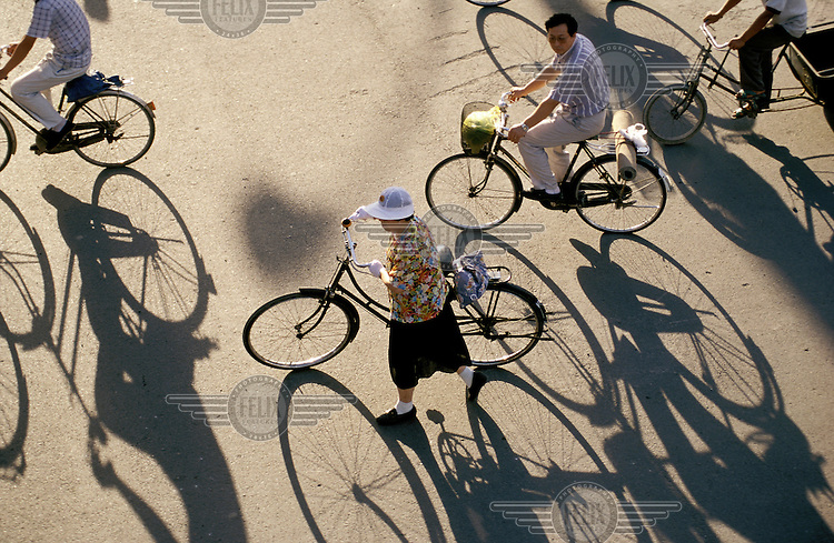 Cyclists and their shadows crossing new highway, late afternoon.