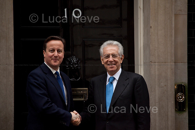 """David Cameron (British Prime Minister) and Mario Monti (Italian Prime Minister) - 2012<br /> <br /> London, 18/01/2012. Mario Monti had his first institutional visit of the UK today, as the new Italian Prime Minister. """"Il Professore"""" arrived at Downing Street at 13:00, where his host David Cameron was waiting, along with a number of prominent Italian and British members of the press. However a series of protocol mishaps ensued. After a friendly first handshake as Mario Monti leaves his car, the British and Italian Prime Ministers take their position at the door of No.10 for the press photo opportunity.  It becomes apparent that no aide has been arranged by Downing Street to take Monti's coat, leaving the Italian Prime Minister fidgeting for an embarrassing while, as Cameron remains frozen, holding out an awkward un-met hand. Later, the famous """"UK First Cat"""" was spotted, waiting outside his house for staff to open the door. Around 14:30, the meeting was seen to end as unconventionally as it had started: Mario Monti walked out of the door of the residence of the British Prime Minister with some of his staff, but without assistance or public send-off by Cameron."""