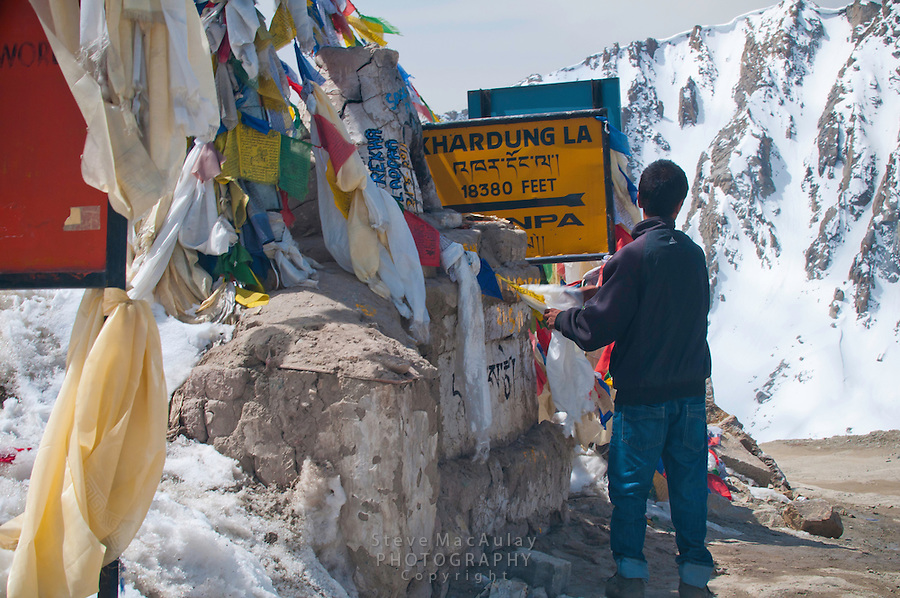 man wrapping prayer flags around marker at Khardung La, at 18,380ft, the summit of the highest motorable road in the world,  Himalayan Mountains, Ladakh, India.