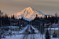 Mount Redoubt catches morning light from the sunrise as morning traffic makes its way through Soldotna, Alaska.
