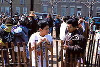 Mexican American dad and son age 38 and 16 at Pilsen Easter Procession.  Chicago Illinois USA