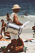 Rio de Janeiro, Brazil. Man selling matte tea from an aluminium barrel on Copacabana beach.