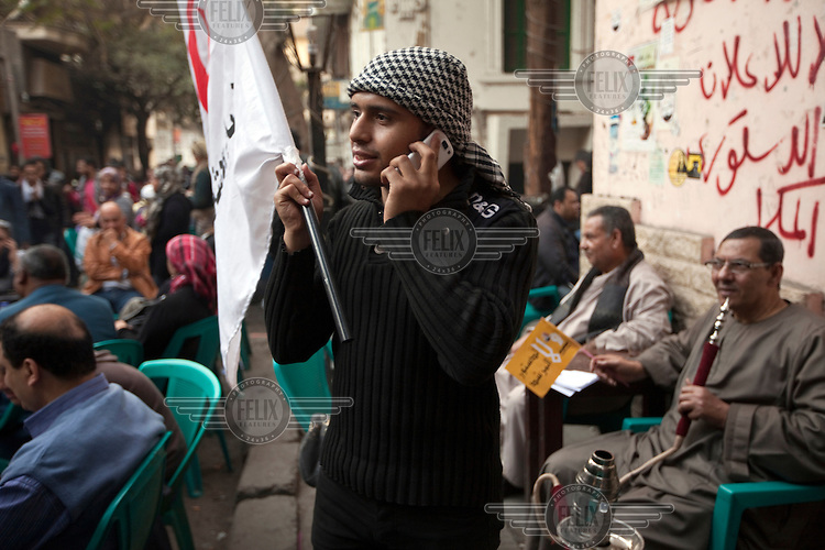 A man with a flag speaks on his mobile phone while others who have been protesting in Tahrir Square come and rest at the Zahrat al-Bustan cafe. /Felix Features