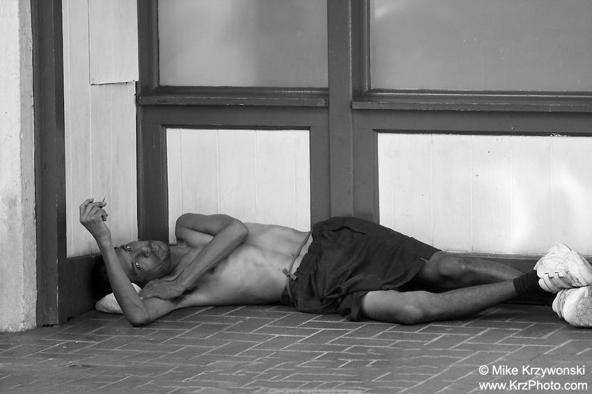 Homeless man lying down on sidewalk in Chinatown, Downtown, Honolulu, Oahu, Hawaii
