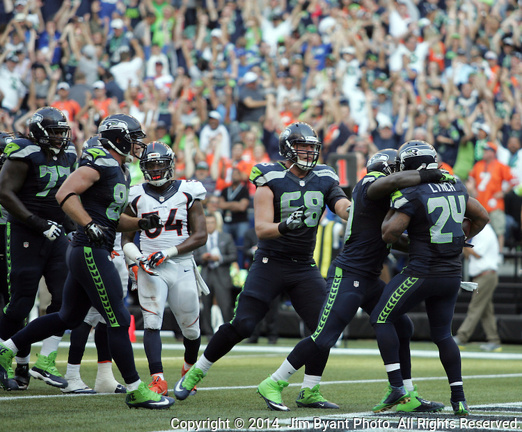 Seattle Seahawks  running back Marshawn Lynch (24) is greeted by teammates after scoring the winning touchdown in overtime  against the Denver Broncos at CenturyLink Field in Seattle, Washington on September 21, 2014. The Seahawks won 26-20 in overtime.    ©2014. Jim Bryant Photo. All rights Reserved.