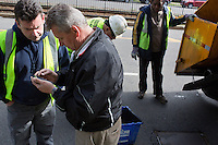 Boston Public Works Department supervisors look at a cell phone while a road crew repairs potholes in Boston, Massachusetts, USA, on April 12, 2012. The city uses a computer system to track public complaints and record work done by city crews to mitigate these complaints.  A supervisor or inspector photographs before and after pictures of the work with a cell phone in addition to making notes about the work done.