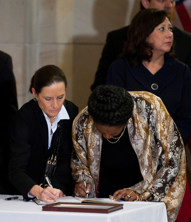 WASHINGTON, DC- Jan. 12: Rep. Jean Schmidt, R-Ohio, and Rep. Sheila Jackson Lee, D-Texas, sign books of well wishes and condolences as members arrive for a Congressional Prayer Service at the U.S. Capitol for the victims of the shooting in Tuscon, Ariz., on Jan. 8 that killed six and injured 14, including Rep. Gabrielle Giffords, D-Ariz., who is recovering after being shot in the head. Labor Secretary Hilda L. Solis is in background. (Photo by Scott J. Ferrell/Congressional Quarterly)