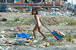 In a Manila neighborhood at the edge of a huge municipal dump, children work recycling items they rescued from the dump....