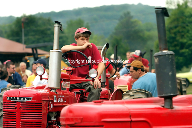 BRIDGEWATER, CT - 20 AUGUST 2005 -082005JS02-- Casey Kinny, 16, of Redding, riding  his 1949 Farmall H tractor, waits for his turn in the antique tractor pull's 4500 pound division Saturday during the annual Bridgewater Country Fair in Bridgewater. The fair continues through today from 9 a.m. to 6 p.m. --Jim Shannon / Republican-American --Bridgewater Country Fair; Bridgewater; Casey Kinny CQ
