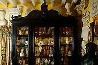 Porcelain objects and books crowd the cluttered bookcase in the drawing room while plaster casts, busts and architectural details cover the walls