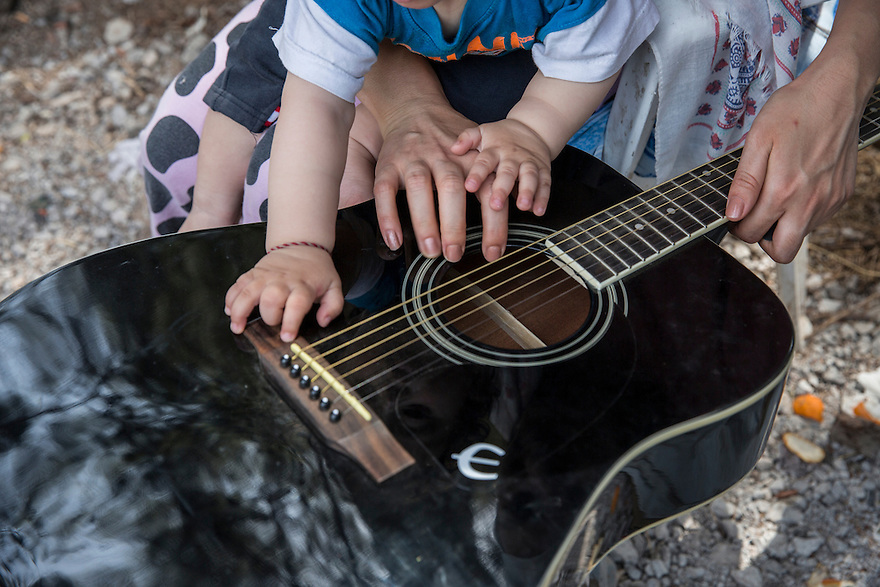 Members of the Noh family with a guitar at Ritsona Camp. Yazidi, immigrated from Iraq due to the ISIS threat nearby. They are now stuck in Greece and living in Ritsona, a refugee camp outside of Athens. PHOTO BY JODI HILTON/PULITZER CENTER