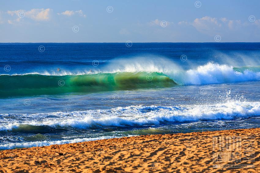 Surfers watch as a beautiful blue green wave breaks onto an empty Kealia Beach in perfect morning light, Kapa'a, Kaua'i.
