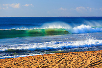Surfers watch as a beautiful blue green wave breaks onto an empty Kealia Beach in perfect morning light, Kapa'a, Kaua'i.