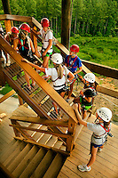 Zip line course participants take flight, zooming through the air over the US National Whitewater Center (USNWC) on the USNWC's zip-lines, part of the facilities high-adventure offerings. The popular outdoor adventure activity lets outdoor enthusiasts be secured into a harness then propelled by gravity along an inclined steel cable. Charlotte, North Carolina's US National Whitewater Center offers multiple zip lines, which vary in height and distance traveled, as well as one of the largest outdoor climbing facilities in the world. The USNWC is a non-profit outdoor recreation facility open to the public for whitewater rafting, kayaking, canoeing, rappelling, zip lining, mountain biking, hiking, climbing and more. The center opened to the public in 2006.