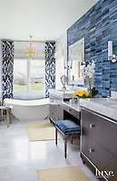 """A wall clad in New Ravenna Marcasite Bricks from Decorative Materials fashions an artful background for custom cabinets decorated with Amerock drawer pulls and topped with marble slabs from Arizona Tile.""<br />
