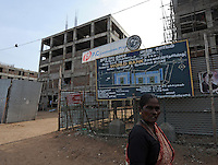 A lady is passing in front of building construction site in Madras, India