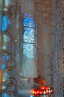 Reflection in the glass of the cabinet of censers, and hand printed wallpaper using gold leaf by Atelier d'Offard, using interlacing patterns reminiscent of the Neo-Romanesque period of the 19th century, in the Bell tower room themed 'Le Merveilleux' or The Supernatural, first floor, in Le Tresor de la Cathedral d'Angouleme, in Angouleme Cathedral, or the Cathedrale Saint-Pierre d'Angouleme, Angouleme, Charente, France. The 12th century Romanesque cathedral was largely reworked by Paul Abadie in 1852-75. In 2008, Jean-Michel Othoniel was commissioned by DRAC Aquitaine - Limousin - Poitou-Charentes to display the Treasure of the Cathedral in some of its rooms, which opened to the public on 30th September 2016. Picture by Manuel Cohen. L'autorisation de reproduire cette oeuvre doit etre demandee aupres de l'ADAGP/Permission to reproduce this work of art must be obtained from DACS.