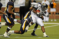 26 December 2010:  FIU running back Darriet Perry (28) continues driving forward despite the effort by Toledo defenders in the fourth quarter as the FIU Golden Panthers defeated the University of Toledo Rockets, 34-32, to win the 2010 Little Caesars Pizza Bowl at Ford Field in Detroit, Michigan.