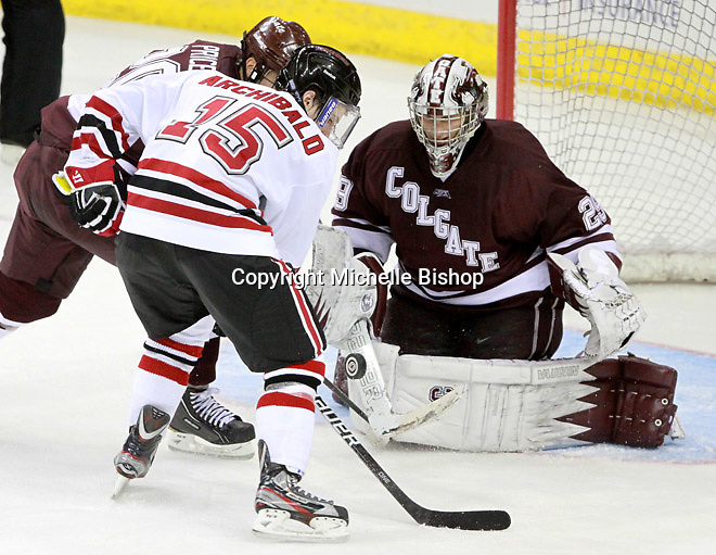 Colgate goalie Eric Mihalik watches the puck as it bounces between  Jeremy Price and Nebraska Omaha's Josh Archibald. (Photo by Michelle Bishop)