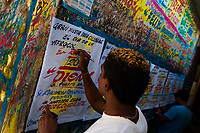 """A Colombian sign painter writes with a brush while working on music party posters in the sign painting workshop in Cartagena, Colombia, 15 April 2018. Hidden in the dark, narrow alleys of Bazurto market, a group of dozen young men gathered around José Corredor (""""Runner""""), the master painter, produce every day hundreds of hand-painted posters. Although the vast majority of the production is designed for a cheap visual promotion of popular Champeta music parties, held every weekend around the city, Runner and his apprentices also create other graphic design artworks, based on brush lettering technique. Using simple brushes and bright paints, the artisanal workshop keeps the traditional sign painting art alive."""
