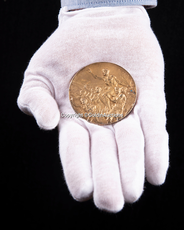 BNPS.co.uk (01202 558833)<br /> Pic: GoldinAuctions/BNPS<br /> <br /> Reverse - Victorious athlete being carried from the stadium by cheering crowd.<br /> <br /> Jesse Owens Berlin Gold medal<br /> <br /> One of the four historic gold medal that Jesse Owens won during the notorious 1936 Berlin Olympics has emerged for sale for the very first time for a whopping £1.6m ($2m)<br /> <br /> Owens won four medals in a golden riposte to the watching Nazi high command during the games throwing the idea of Aryan supremacy back into Hitler's face.<br /> <br /> Of the quartet of prizes - awarded for the 100 meters, 200 meters, long jump and 4×100-meter relay - only one has ever been sold before.<br /> <br /> The award is going under the hammer with Goldin Auctions of Camden County, New Jersey.