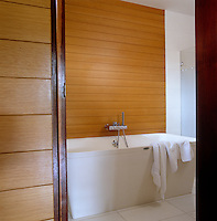 The contemporary freestanding bath is set against an oak tongue and groove wall