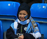 26th January 2020; Etihad Stadium, Manchester, Lancashire, England; English FA Cup Football, Manchester City versus Fulham; a young Manchester City fan with his face painted in team colours looks on from the stands