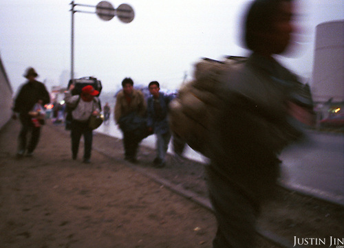 Wei and his family and friends carry bags towards the train station in Beijing, on their way to home in Sichuan...Picture taken April 1999.Copyright Justin Jin