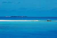 Fishing boat anchored on a white sand beach with a tropical island in the background, Maldives.
