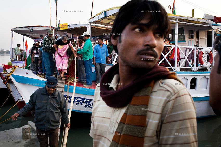 Indian tourists arrive by boats in droves on Gosaba island, Sundarban, West Bengal, India, on 18th January, 2012. The Sundarban islands and mangroves are sinking, say experts, due to climate change. Locals say they are overwhelmed by tourists' trash that affect the mangroves and sudden changes in weather patterns that have caused such damage that they continue to struggle to recover. One of the islands, once inhabited, has slowly sunk. Photo by Suzanne Lee for The National (online byline: Photo by Szu for The National)
