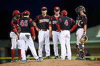 Batavia Muckdogs manager Angel Espada (4) talks with pitcher LJ Brewster as (L-R) Anfernee Seymour, Giovanny Alfonzo (hidden), Joseph Chavez (46), Eric Fisher and Blake Anderson look on during a game against the Mahoning Valley Scrappers on July 3, 2015 at Dwyer Stadium in Batavia, New York.  Batavia defeated Mahoning Valley 7-4.  (Mike Janes/Four Seam Images)