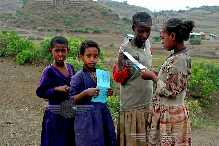 Schoolgirls compare school report cards on the last day of term.