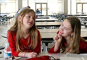 Sophia Salem 8 and her big sister Selene 13 share a  ight moment while doing their homework in the cafeteria of the Pennridge High School in Perkasie, Pa., during a wrestling match on Sunday February 26, 2006, in which their brothers, twins Sam and Jake 12 compete. The Salem children, 3 sets of twins, are from Russia. Sophia and twin Joseph were adopted at 11 months of age. The other twins were adopted just 20 months ago. All children are thriving in school and socially. photo by jane therese