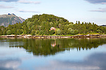Isolated coastal house on small wooded island near Ornes, Nordland, Norway