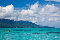Tahitian man paddling small outrigger canoe off Tahaa island with Raiatea in background