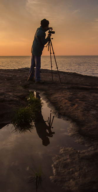 A photographer makes imagaes on a rocky point on Lake Superior at Big Bay State Park, Ashland County, Wisconson