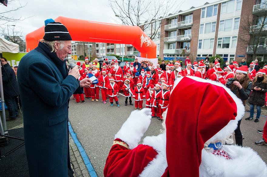 Nederland, Amsterdam, 21 dec 2014<br /> Santa Run op het Gelderlandplein, Amsterdam. Freek de Jonge leest een kerstgedicht voor als start van de run.<br /> De Santa Run is een fun-run van 3000 meter en wordt gelopen door als kerstman verklede renners die daarmee geld ophalen voor, in dit geval, het Leerorkest en het Liliane Fonds. De Rotary Club organiseert wereldwijd Santa Runs om geld in te zamelen voor goede doelen.<br /> Foto: (c) Michiel Wijnbergh