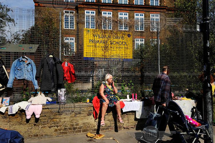 Woman running a bric-a-brac stall on Cheshire Street in London's Brick Lane market.