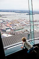 Young Boy Looking Over Auckland at the Top of the Sky Tower, North Island, New Zealand. The Sky Tower is one of the main tourist attractions in Auckland, and at 328 meters tall, is the highest building in the southern hemisphere. It offers revolving cafes, bars and restaurants, the adrenaline filled Sky Jump and Sky Walk, and unrivalled views of Auckland and the surrounding islands from the 220 meter viewing platform.