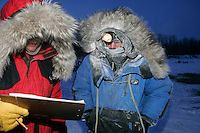 Wednesday March 7, 2007     Rookie Tom Lesatz checks in at the Nikolai checkpoint on Wednesday in 35 below temperatures with volunteer checker Jim Gallea