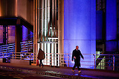 Pedestrians walk past the Lloyds Building in the City of London at night.