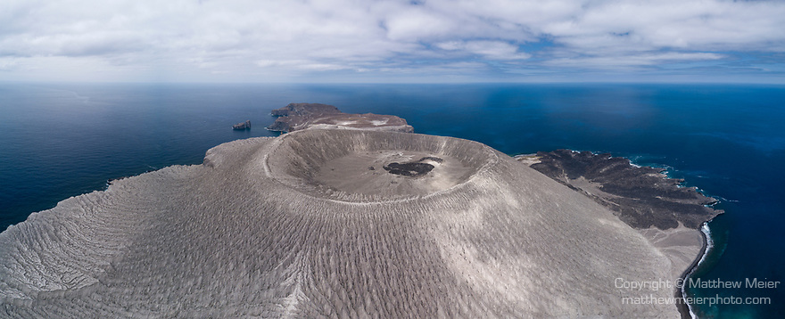 San Benedicto Island, Revillagigedos Islands, Mexico; a panoramic aerial view of the cinder cone and lava flow into the Pacific ocean from the 1952 volcanic eruption, with the Socorro Vortex liveaboard dive boat, anchored at El Canon dive site
