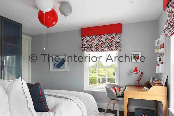 A child's bedroom painted grey with accents of red and dark blue in the furnishings.  Balloon lights with pull chords are a practical and fun feature above the bed