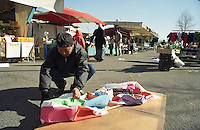 Milano, mercato rionale al quartiere Bruzzano, periferia nord. Immigrato filippino laureato in ingegneria meccanica raccoglie la sua mercanzia --- Milan, local market at Bruzzano district, north periphery. Immigrant from Philippine with a degree in automotive engineering collects his merchandise