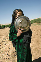 Twelve year old Zubayda hides her face with a tin plate.