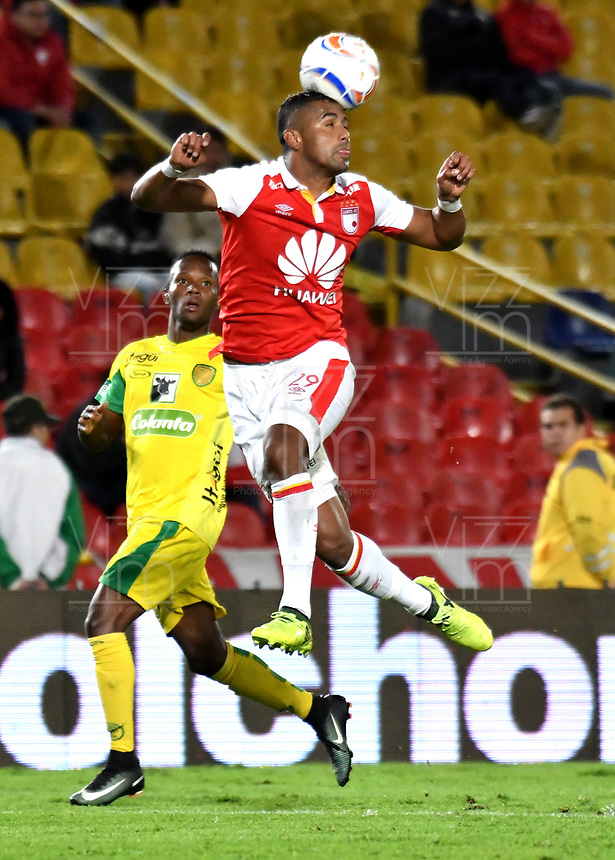BOGOTA - COLOMBIA, 22-04-2018: Carlos Henao (Der.), jugador de Independiente Santa Fe, salta a disputar el balón con Jhon Sánchez (Izq.) jugador de Leones F. C., durante partido de la fecha 17 entre Independiente Santa Fe y Leones F. C., por la Liga Aguila I 2018, en el estadio Nemesio Camacho El Campin de la ciudad de Bogota. / Carlos Henao (R) player of Independiente Santa Fe, jumps to struggle for the ball with Jhon Sanchez (L) player of Leones F. C., during a match of the 17th date between Independiente Santa Fe and Leones F. C., for the Liga Aguila I 2018 at the Nemesio Camacho El Campin Stadium in Bogota city, Photo: VizzorImage / Luis Ramirez / Staff.