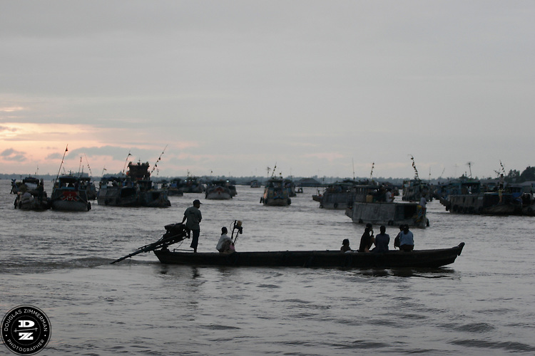 Just after sunrise, a motorboat brings passengers to some of the boats selling produce on the Bassac River in the Mekong Delta in Chau Doc, Vietnam.  The Mekong Delta has long been the watery thoroughfare for the many villages that dot the riversides of the delta.  Many of the villages have floating markets where people can buy produce and other items from wholesalers.  Photograph by Douglas ZImmerman